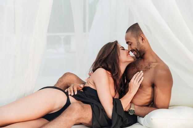 Sensuel jeune couple s'embrassant et embrassant sur un lit blanc