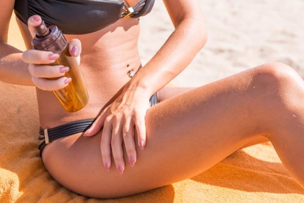 Sensuelle femme mince appliquant de l'huile de bronzage