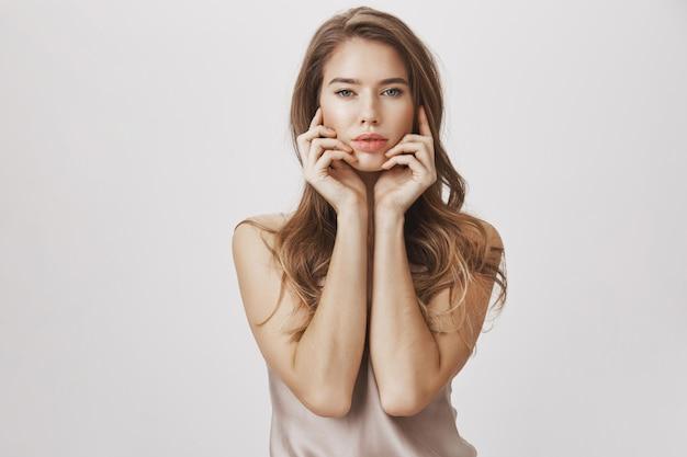 Sensuelle femme passionnée touchant le visage