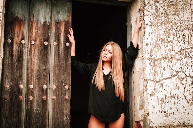 Sensuelle fille blonde en chemise noire attend près d'une porte