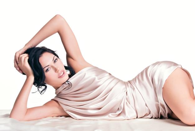 Sensuelle jeune femme avec beau corps dans la soie beige sur mur blanc