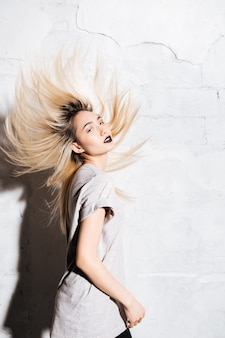 Sensuelle jeune femme blonde dansant et secouant ses cheveux