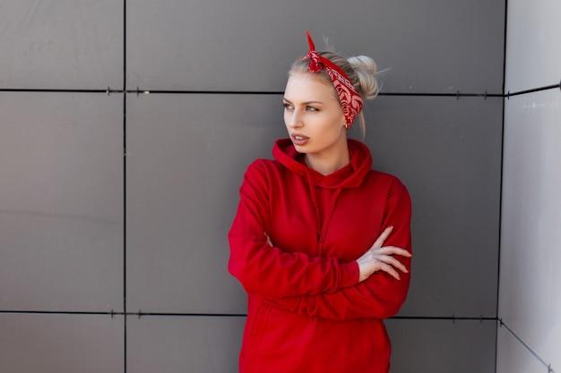 Sensuelle jeune femme blonde moderne dans un bandana tendance rouge dans un sweat à capuche élégant rouge posant à l'extérieur près d'un mur vintage un jour d'été