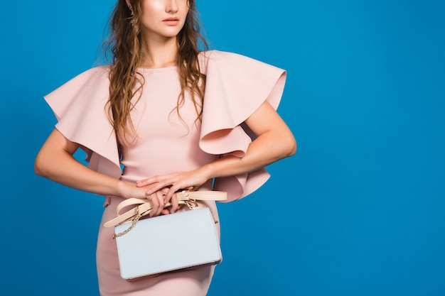 Sensuelle jeune femme sexy élégante en robe de luxe rose, tendance de la mode estivale, style chic, fond de studio bleu, tenant le sac à main à la mode