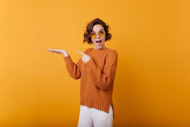 Sensuelle jolie fille porte des lunettes jaunes rondes posant. photo intérieure d'une femme positive gracieuse exprimant le bonheur.