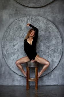 Sensuelle séduisante jeune femme rousse avec des jambes sexy dans le corps posant sur un mur de pierre à la surface