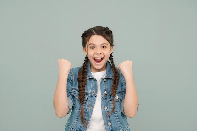 Sentez-vous bien, souriez bien. une fille heureuse célèbre la victoire. le petit gagnant fait un geste gagnant. hygiène dentaire. produits d'hygiène bucco-dentaire. remplissage des dents. service de santé dentaire. excellence dentaire. grandir en souriant.