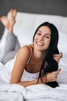 Sentez-vous libre de faire n'importe quoi! belle jeune femme jouant avec ses cheveux et regardant la caméra