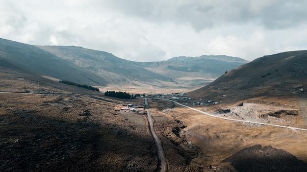 Sentier au milieu des montagnes près d'une maison sous un ciel nuageux