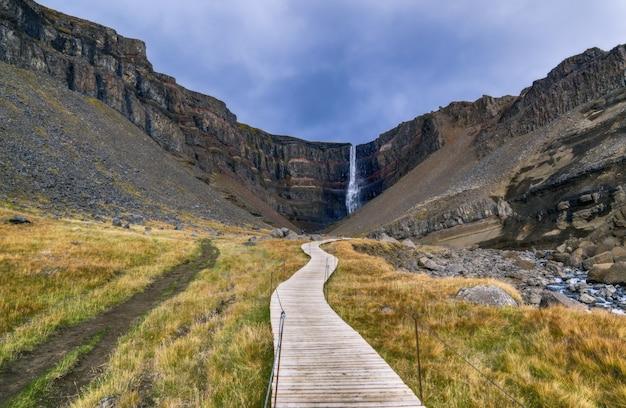 Sentier en bois brun sur champ d'herbe verte près de la montagne rocheuse brune sous les nuages blancs pendant la journée