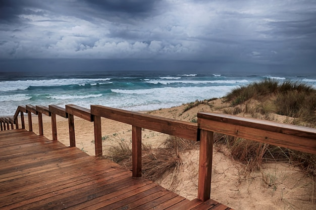 Sentier en bois sur la plage par les vagues de l'océan à couper le souffle sous le ciel nuageux