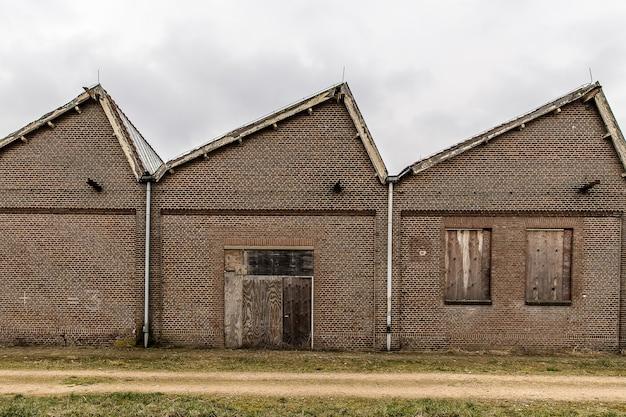 Sentier près d'un bâtiment en brique avec un ciel nuageux dans le