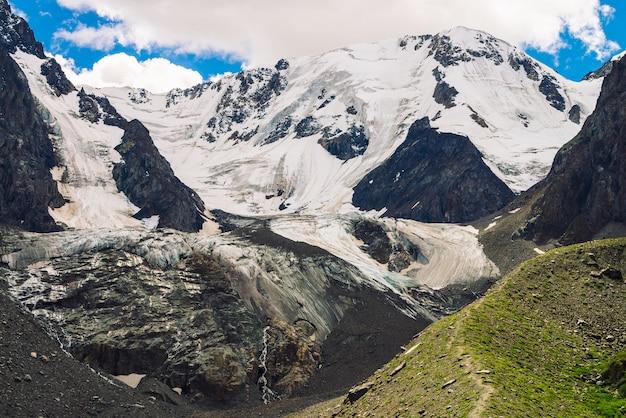 Sentier de randonnée mène aux énormes montagnes enneigées par journée ensoleillée. magnifique glacier au soleil. ruisseaux d'eau sur la montagne. végétation riche des hauts plateaux. paysage minimaliste atmosphérique ensoleillé de la nature.
