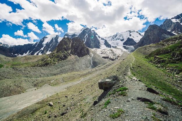 Sentier de randonnée mène aux énormes montagnes enneigées par journée ensoleillée.