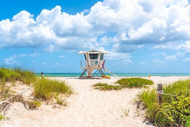 Sentier vers la plage avec cabane de sauveteur et océan sur fond à fort lauderdale, floride, etats-unis