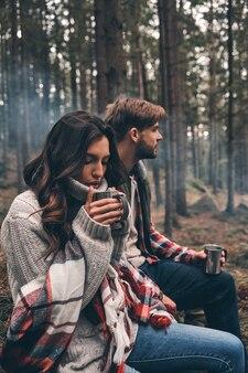 Sentir la chaleur. jeune beau couple dégustant des boissons chaudes assis dans la forêt