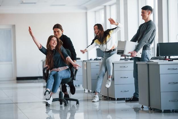 Sentir la liberté. s'amuser au bureau. les jeunes font une pause et conduisent en utilisant un siège