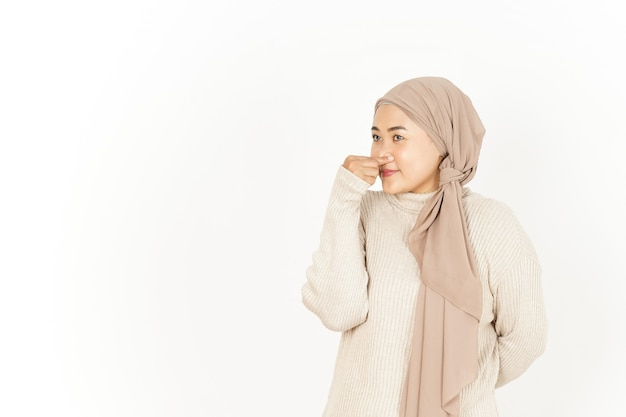 Sentir quelque chose de puant et dégoûtant de la belle femme asiatique portant le hijab isolé sur blanc
