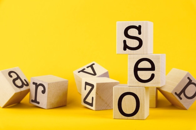 Seo, optimisation des moteurs de recherche, blocs de cube en bois de texte sur jaune
