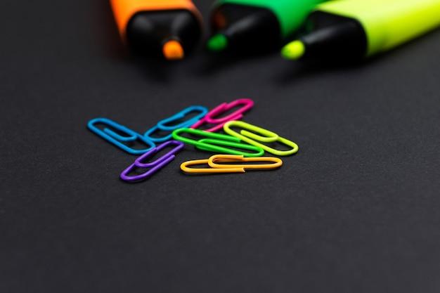 Séparateurs de texte de différentes couleurs et trombones sur un bureau noir