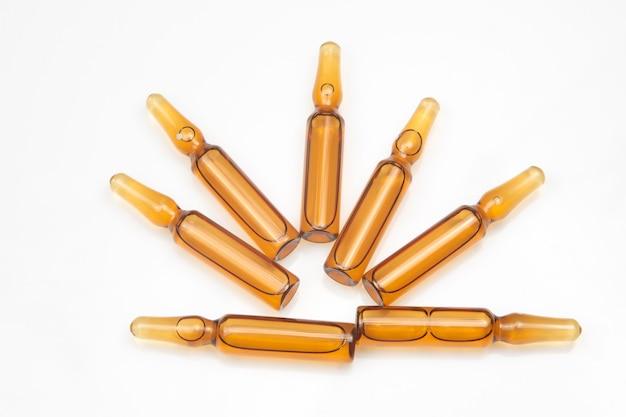 Sept ampoules en verre médical pour drogues injectables sur fond blanc