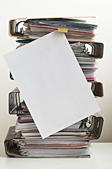 Sept dossiers avec des documents empilés en tas sur la table