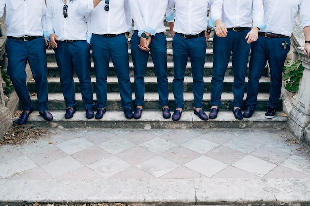 Sept meilleurs hommes de palefreniers en pantalon bleu et chaussures identiques se tiennent sur les escaliers en gros plan