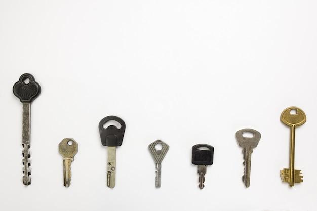 Sept types de clés de porte de forme différente se trouvent dans une rangée sur un fond blanc sous écrêtage