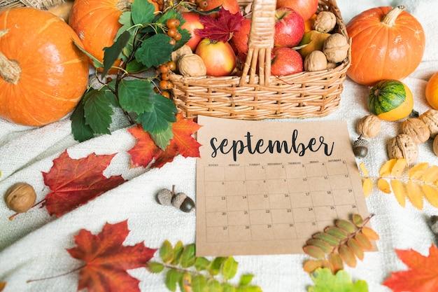 Septembre avec panier de pommes mûres et citrouilles, noix, glands et feuilles d'automne à proximité