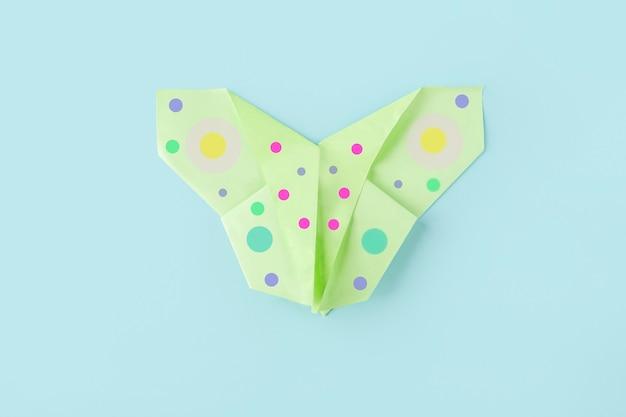 Septième étape de la fabrication d'un papillon en papier origami avec du papier vert, des ciseaux sur fond bleu