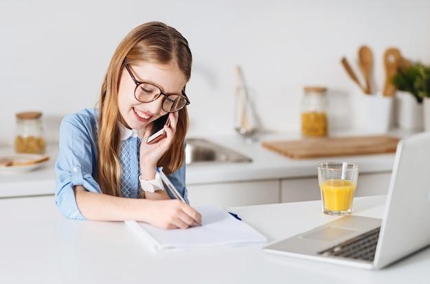 Serait-ce difficile. optimiste charmante fille magnifique discutant de certains détails du futur test avec son amie alors qu'elle était assise à la table dans une cuisine et travaillait sur son devoir à domicile
