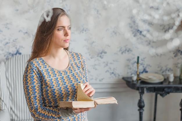 Serein, jeune femme, debout, contre, papier peint, tenant livre, dans main