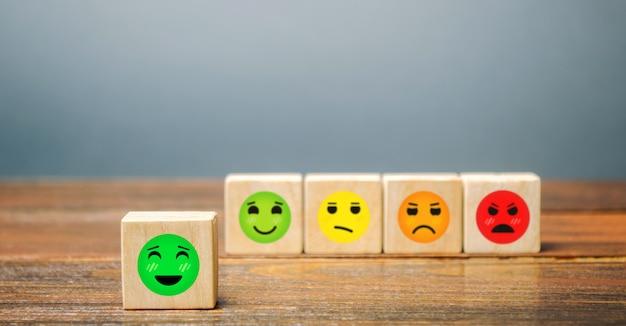 Une série de blocs aux visages joyeux à fâchés. visage de bonheur sélectionné.