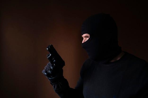 Série d'un cambrioleur de race blanche par effraction dans une maison avec un pistolet à la main.