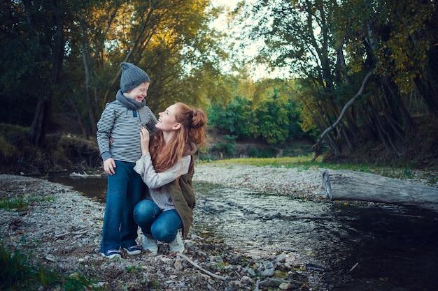 Une série sur les cheveux roux heureux. la sœur aînée et le frère et la sœur cadets. parc, automne, rivière. moment heureux