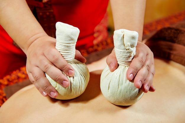 Série de massages thaïlandais: massage du dos et des épaules, massage aux herbes et au spa, médecine naturelle, ingrédient à base de plantes comme le bâton de cannelle, le curcuma, la bergamote