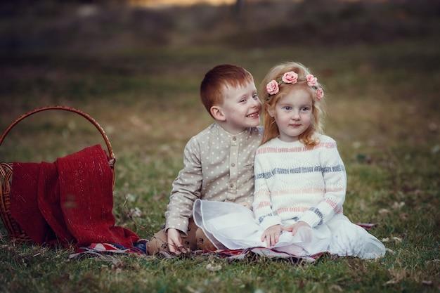 Une série de photos d'enfants aux cheveux roux. fille et garçon dans la nature, coucher de soleil, automne. moment heureux