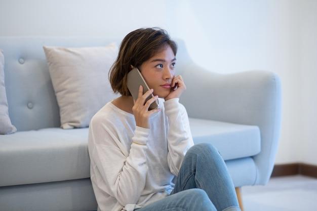 Sérieuse cliente asiatique pensive qui parvient à l'assistance par téléphone