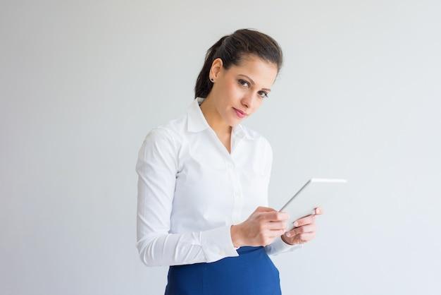 Sérieuse confiante jeune femme d'affaires à l'aide de tablette numérique et en regardant la caméra.