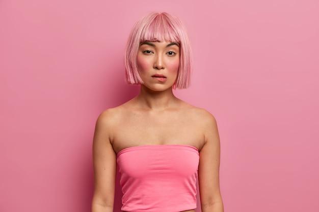 Sérieuse femme adorable avec une apparence orientale, une coiffure bob rose, porte un débardeur, mord les lèvres et regarde directement, pense à une bonne décision, a une expression mystérieuse. fille de mode