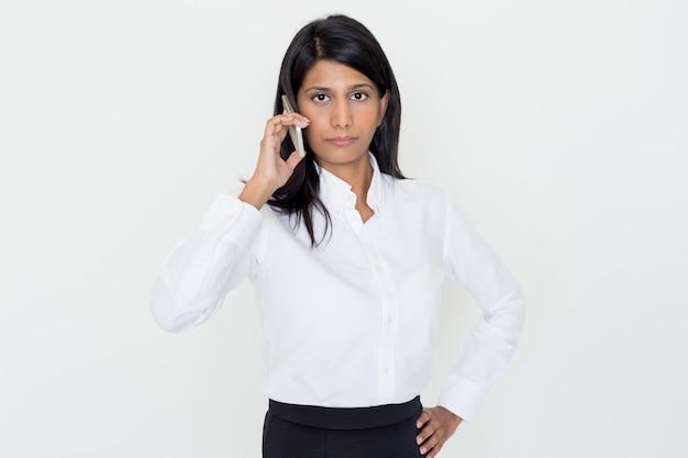 Sérieuse femme d'affaires indienne appelant sur smartphone