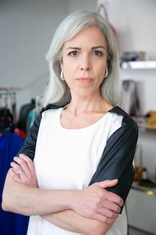 Sérieuse femme aux cheveux blonds caucasienne debout avec les bras croisés près de la crémaillère avec des robes dans un magasin de vêtements, regardant la caméra et souriant. concept de client de boutique ou de vendeur
