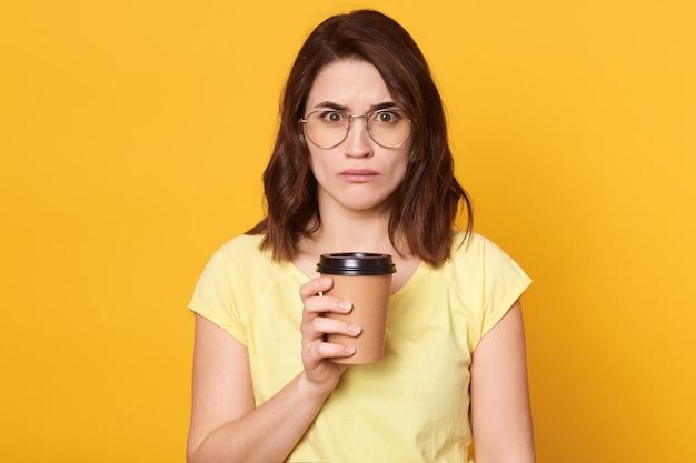 Sérieuse femme aux cheveux noirs tenant une tasse de café, porte un t-shirt décontracté et des lunettes