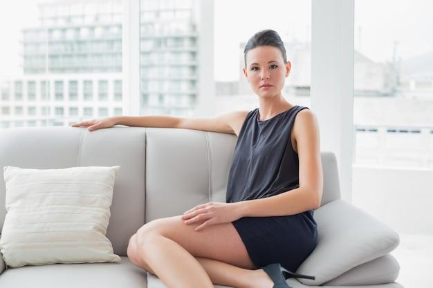 Sérieuse femme bien habillée, assis sur le canapé à la maison