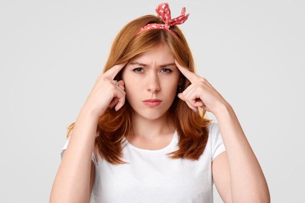 Sérieuse femme concentrée, garde les doigts sur les tempes, essaie de se concentrer sur certaines informations