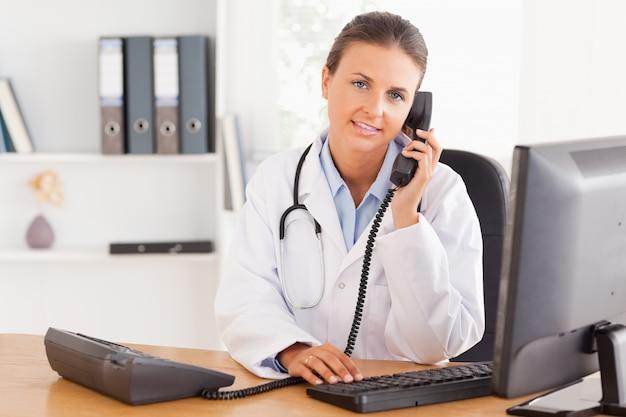 Sérieuse femme médecin au téléphone