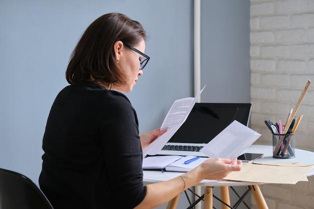 Sérieuse femme mûre tenant des papiers d'affaires en mains documents reçus dans des enveloppes par courrier