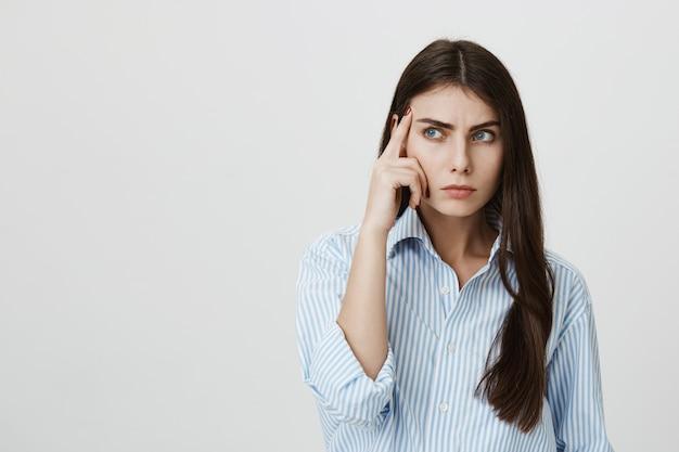 Sérieuse femme séduisante pensant, regardez de côté concentré