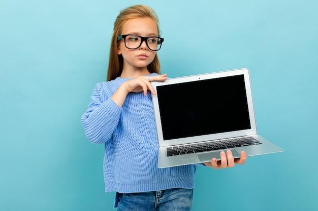 Sérieuse fille européenne tenant un ordinateur dans ses mains avec l'écran vers l'avant avec une maquette bleu clair