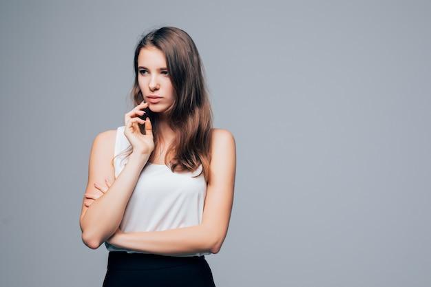 Sérieuse fille sexy en robe moderne de mode pose en studio isolé sur fond blanc